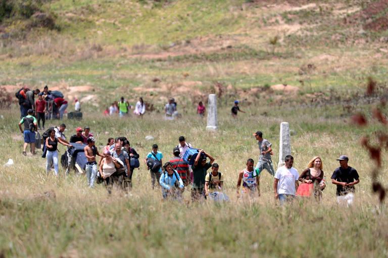 Pessoas tentam atravessar fronteira entre Venezuela e Brasil em Pacaraima, Roraima