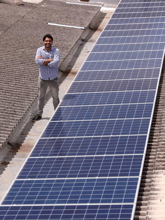 Vinicius Ferraz com placa instalada no teto da sede da Solar 21, em Brasília