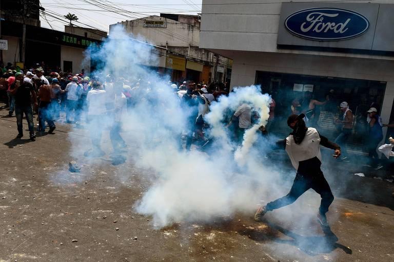 Manifestante joga bomba de gás lacrimogêneo contra policiais venezuelanos em San Antonio del Tachira