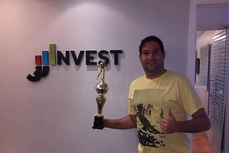 Empresário segura troféu em frente ao letreiro com o nome da empresa