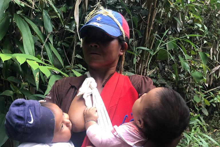 Indígena da etnia pemón foge em trilha de mata para o Brasil carregando os filhos gêmeos
