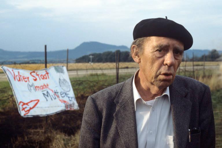 Homem com paletó e boina com cartaz ao fundo