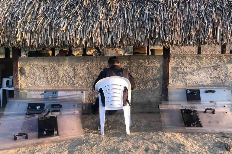 Guarda pemón em posto de vigilância indígena ao lado de pilhas de escudos confiscados de militares da Guarda Nacional, em Santa Elena de Uairén, Venezuela.