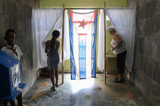 Voters cast their votes at a polling station during a constitutional referendum in Havana