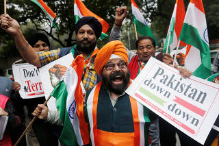 People hold national flags and placards as they celebrate after Indian authorities said their jets conducted airstrikes on militant camps in Pakistani territory, in New Delhi