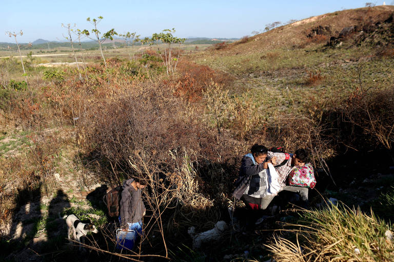 A Brazilian Family walks through a field as they try to cross the border between Venezuela and Brazil