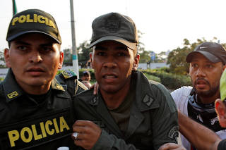 A member of the Venezuelan National Guard who defected to Colombia is escorted by a Colombian policeman near the Simon Bolivar cross-border bridge between Venezuela and Colombia, in Cucuta