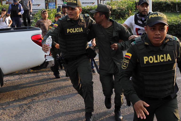Soldado da Guarda Nacional venezuelana que desertou para a Colômbia é escoltado por um policial colombiano em Cúcuta, Colômbia