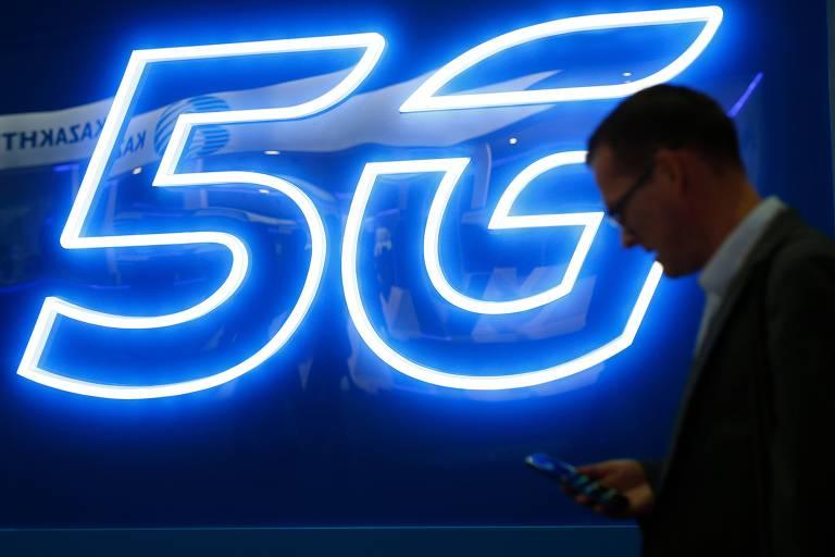 Um homem mexendo no celular passa na frente de um sinaleiro luminoso escrito 5G