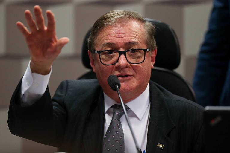 Ministro da Educação veste terno, fala em frente a microfone e tem o braço direito levantado com as mãos abertas