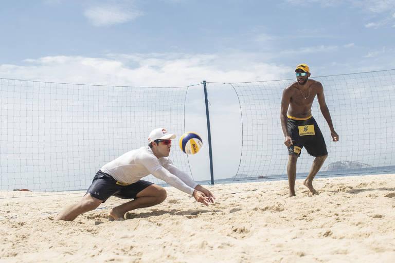 Ao lado do parceiro Evandro, Bruno Schmidt defende uma bola durante treino na praia do Leblon