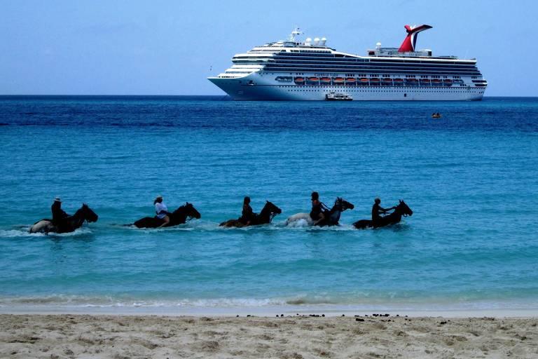 Pessoas andam a cavalo dentro da água em praia