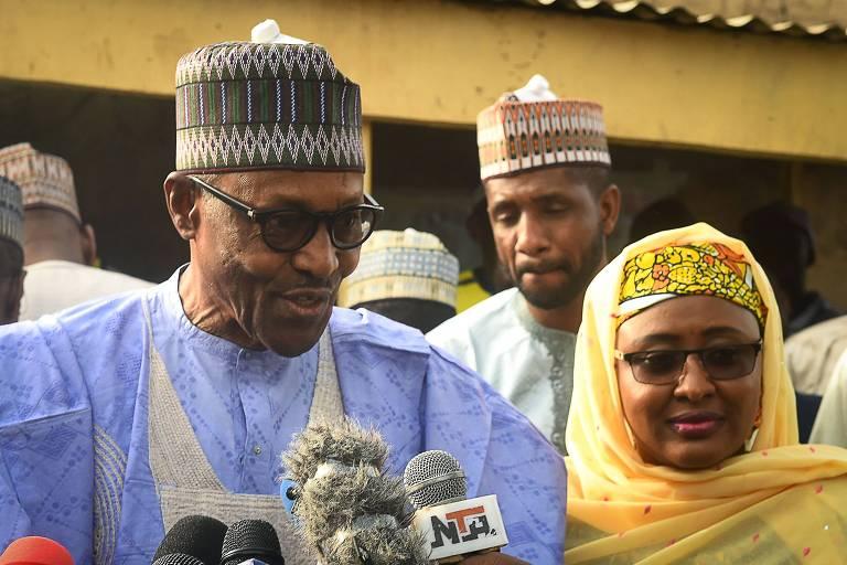 Muhammadu Buhari veste trajes tradicionais e fala em microfone de emissoras de TV
