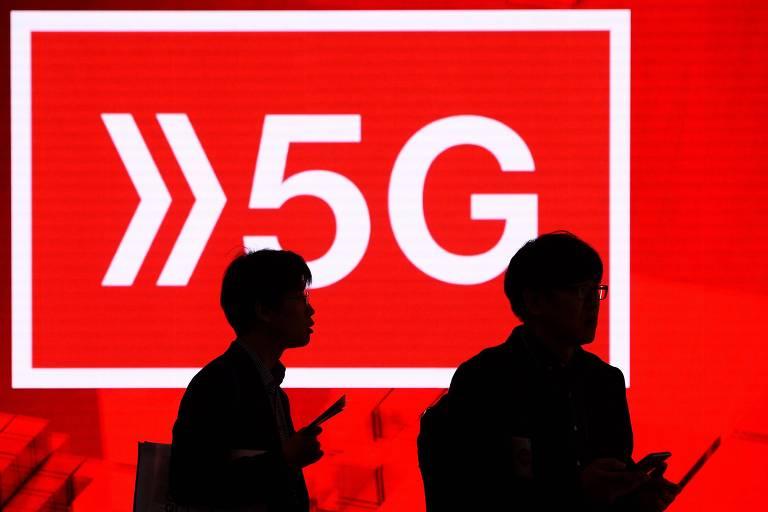 Duas pessoas sentadas em frente a placar com escrito 5G