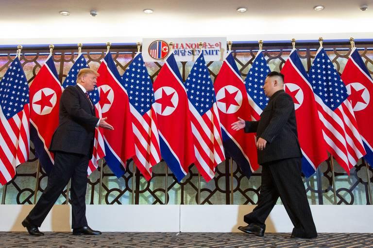 Donal Trump e o ditador Kim Jong Un TOPSHOT - US President Donald Trump (L) shakes hands with North Korea's leader Kim Jong Un em reunião em Hanói, Vietnã