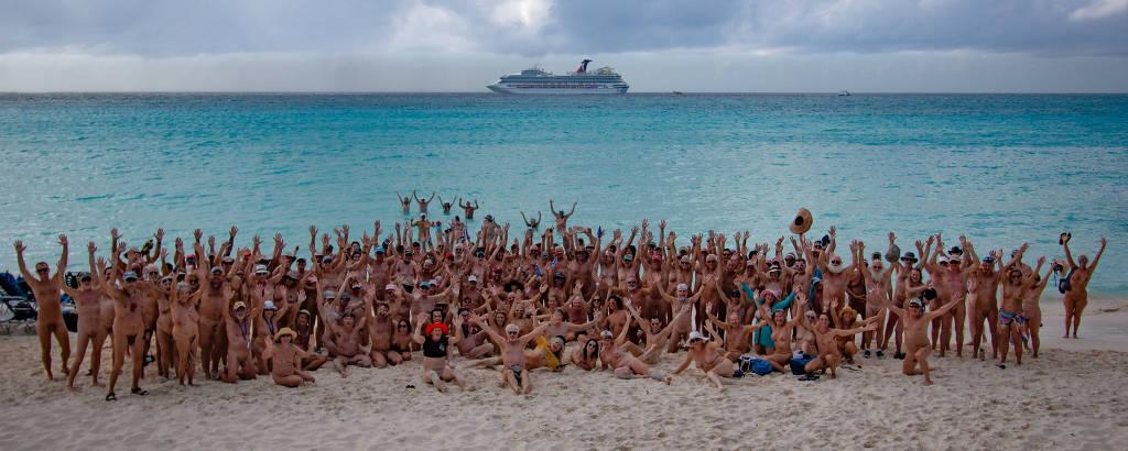 Pessoas peladas em praia, com navio ao fundo