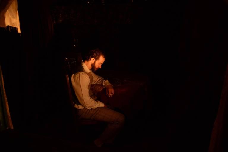 Homem reflete em cenário escuro