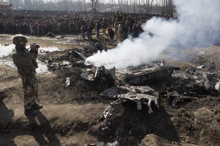 Soldado indiano fotografa destroços de uma aeronave da Índia