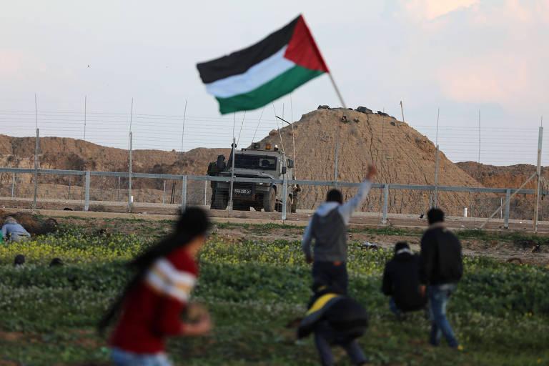Homem segura bandeira palestina durante um confronto com as tropas israelenses na fronteira entre Gaza e Israel