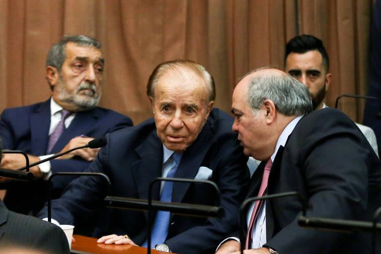 Três homens de terno, menem ao centro, conversam dentro de sala com painéis de madeira nas paredes; eles estão sentados à uma mesa de madeira retangular, um ao lado do outro
