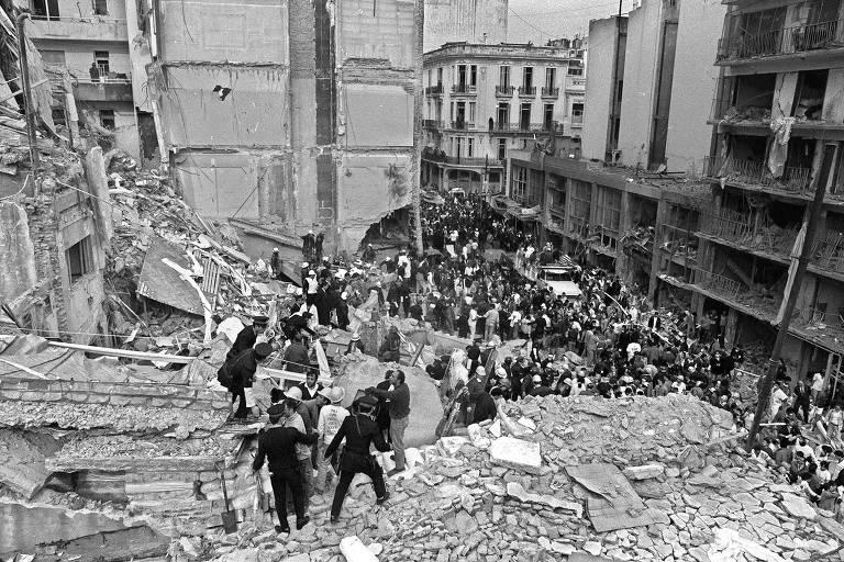 Foto em preto e branco de 18 de julho de 1994 mostra bombeiros e policiais buscando sobreviventes nos escombros da sede da Associação Mutual Israelense Argentina (Amia), em Buenos Aires, após explosão de uma bomba