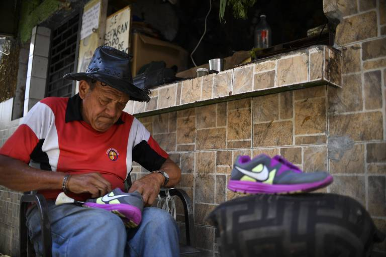 Sapateiro faz reparos em tênis em uma rua de Caracas, na Venezuela