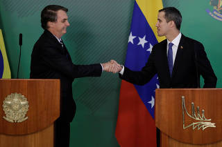 Venezuelan opposition leader Juan Guaido shakes hands with Brazil's President Jair Bolsonaro after a meeting in Brasilia