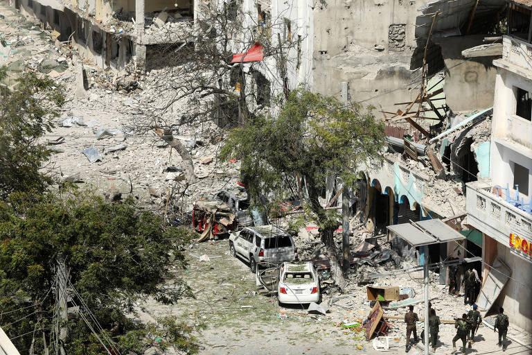 Combatentes das forças especiais somalis são vistos ao lado de prédios destruídos
