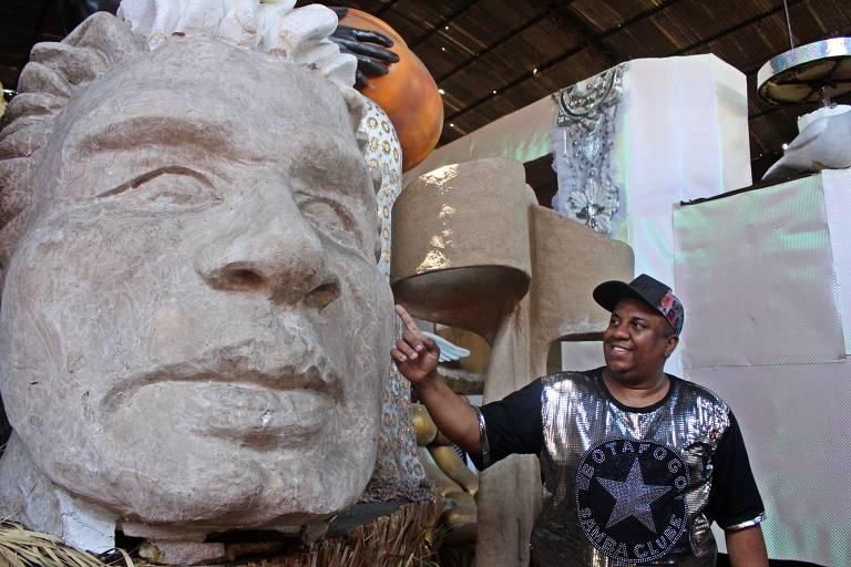 O carnavalesco Tom Santos, da Botafogo Samba Clube, ao lado do busto do jogador Túlio Maravilha