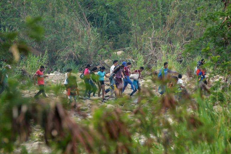 Migrantes venezuelanos cruzam fronteira por rotas ilegais próximas ao rio Táchira para chegar à cidade colombiana de Cúcuta