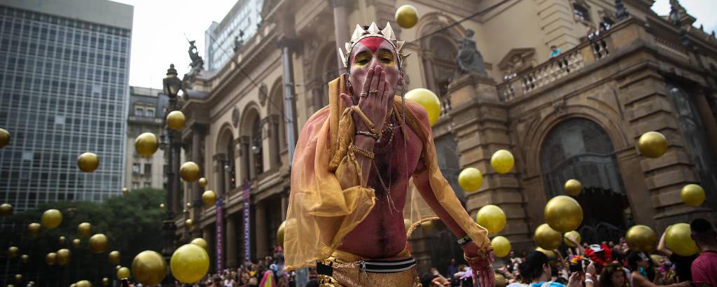 Folião sem camisa, de coroa e com legging dourada manda beijo para a câmera em primeiro plano; em segundo plano, diante do edifício do Theatro Municipal, foliões dançam e brincam com dezenas de grandes bolas plásticas douradas