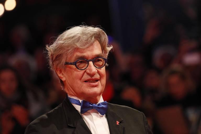 Foto mostra o cineasta Wim Wenders com gravata borboleta e óculos de armação azuis