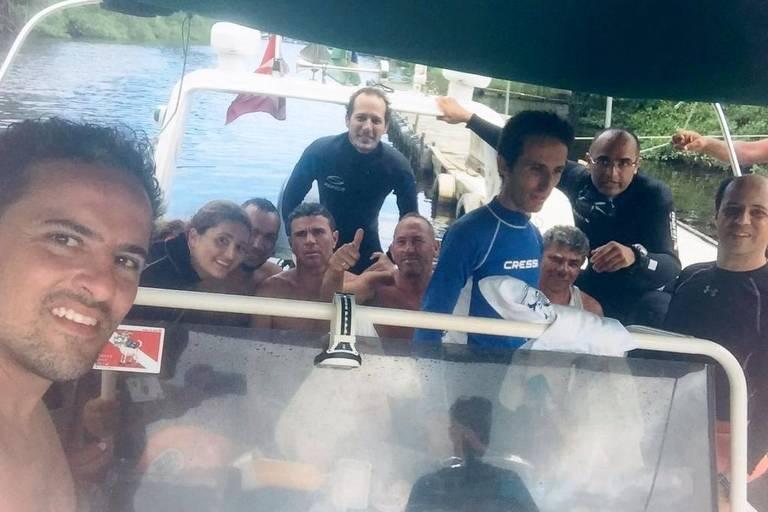 Dez pessoas numa lancha, alguns sentados, outros de pé. Os de pé vestem roupas de mergulho