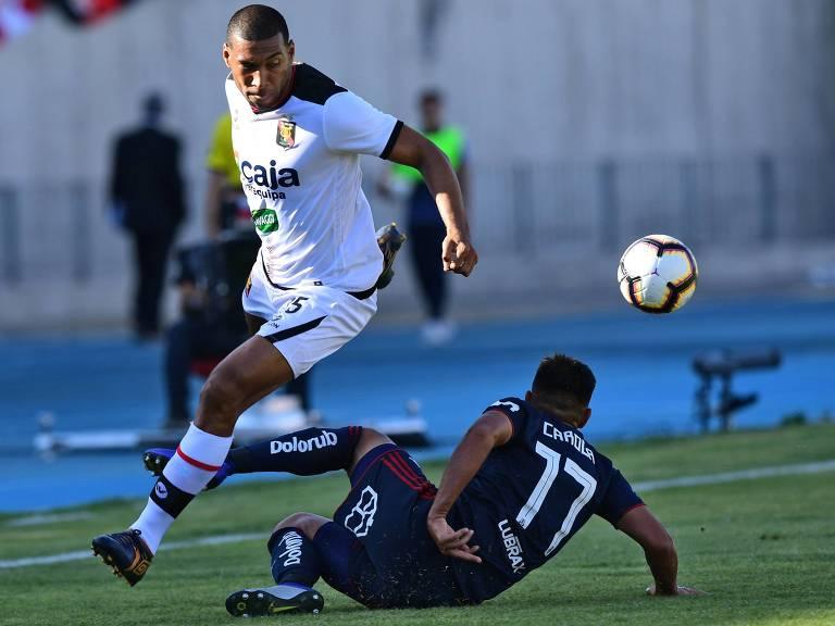 Pablo Labrin passa por marcador da Universidad de Chile durante partida da Libertadores