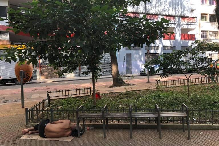 Morador de rua dorme deitado em pedaço de papelão, junto a canteiro de gramado na praça Dom José Gaspar, no centro de SP