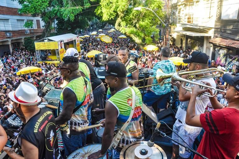 Músicos tocam percussão e metais em cima de trio elétrico para uma multidão em uma rua no centro de Porto Alegre