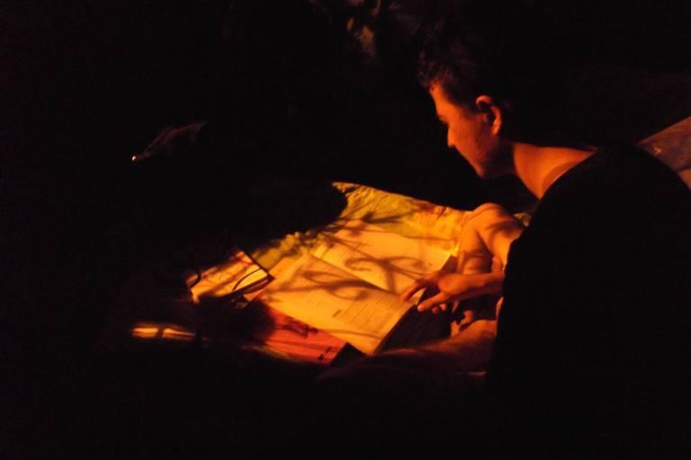 O rapaz está sentado numa cama, num quarto escuro, em que apenas o livro aberto em frente a ele está iluminado pelo poste