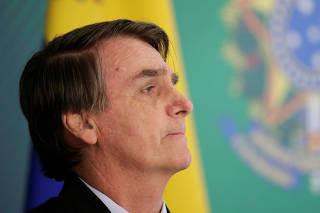 Brazil's President Jair Bolsonaro reacts during a press statement near Venezuelan opposition leader Juan Guaido after a meeting in Brasilia
