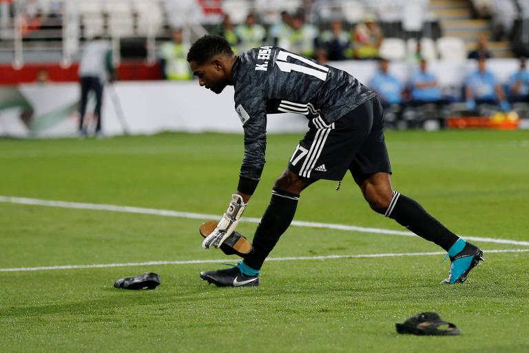 Khalid Eisa, goleiro dos Emirados Árabes, retira sapatos atirados por torcedores no campo após gol do Qatar, na semifinal da Copa da Ásia