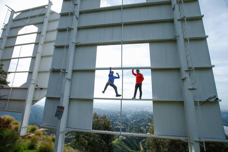 """Alex Honnold (esq.) e o diretor Jimmy Chin, do documentário """"Free Solo"""", escalam e posam na letra H do letreiro de Hollywood"""