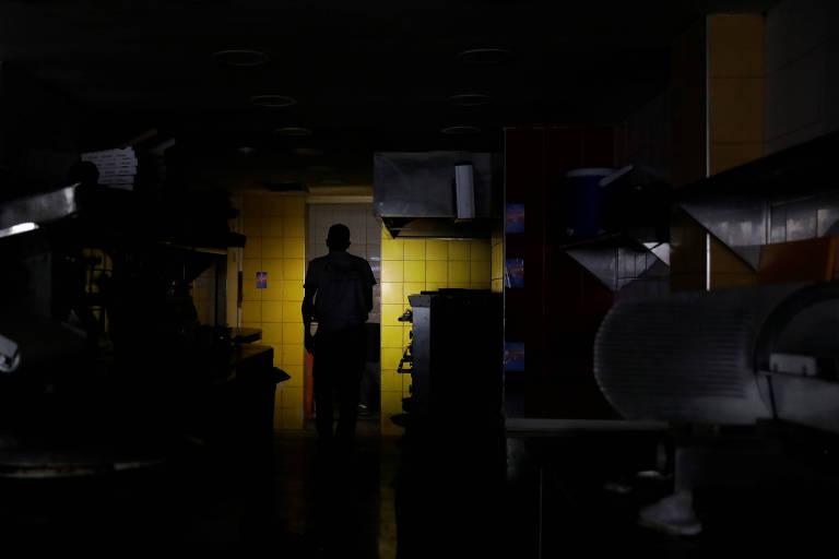 Homem usa telefone celular como lanterna em cozinha de restaurante durante apagão em Caracas