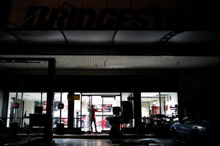A man stands inside a mechanic garage during a blackout in Caracas