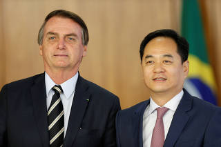 Brazil's President Jair Bolsonaro stands with Chinese Ambassador in Brasilia Yang Wanming during the credentials presentation ceremony of several new diplomats, at Planalto Palace in Brasilia