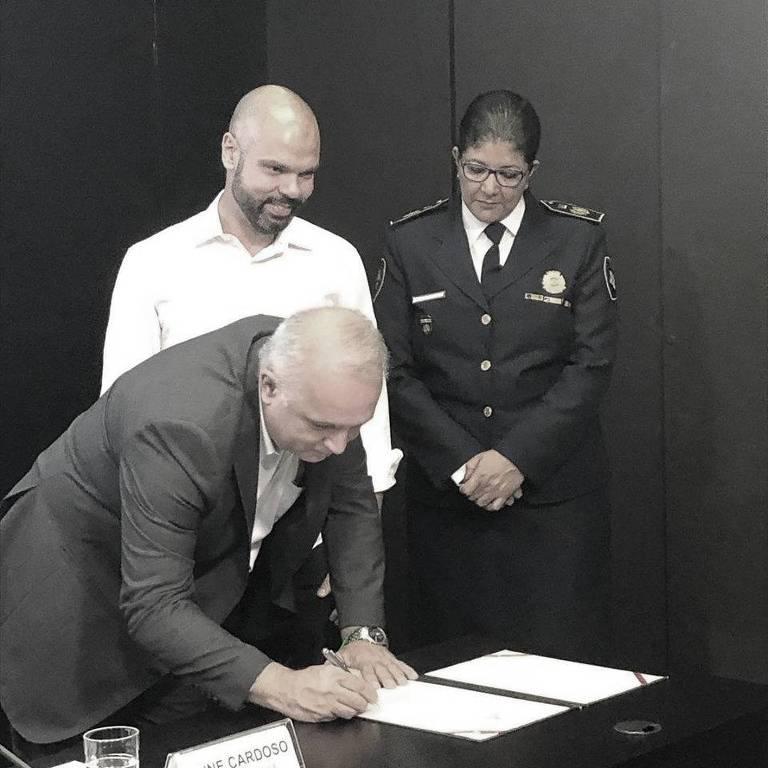 O secretário de Segurança Urbana de São Paulo, José Rodrigues de Oliveira, assina a nomeação da nova comandante-geral da GCM, Elza Paulino de Souza (dir.), ao lado do prefeito Bruno Covas (PSDB)
