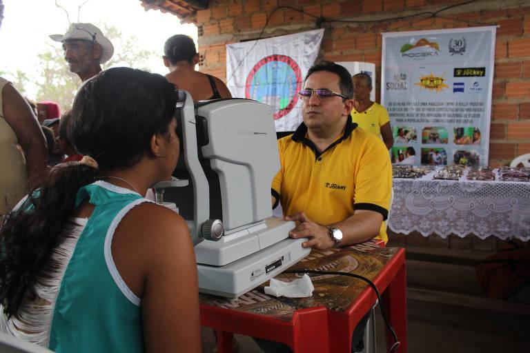 """O empresário Delfino Vieira analisa olho de moradora no assentamento Poços dos Negros, em Altos (PI), durante atividade do projeto social """"De olho na trilha"""", em 2017"""