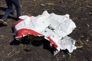People walk past a part of the wreckage at the scene of the Flight ET 302 plane crash, near the town of Bishoftu