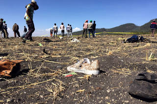 People walk at the scene of the Flight ET 302 plane crash, near the town of Bishoftu