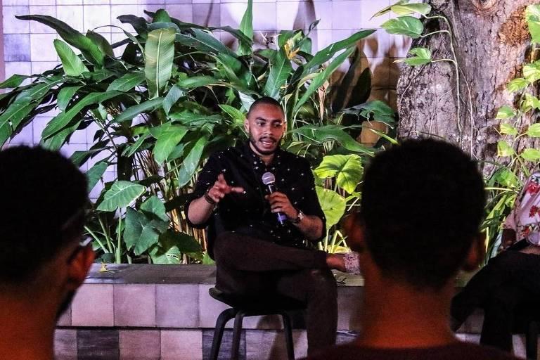 O escritor e publicitário Ale Santos fala para uma plateia, sentado em uma cadeira, com plantas atrás dele