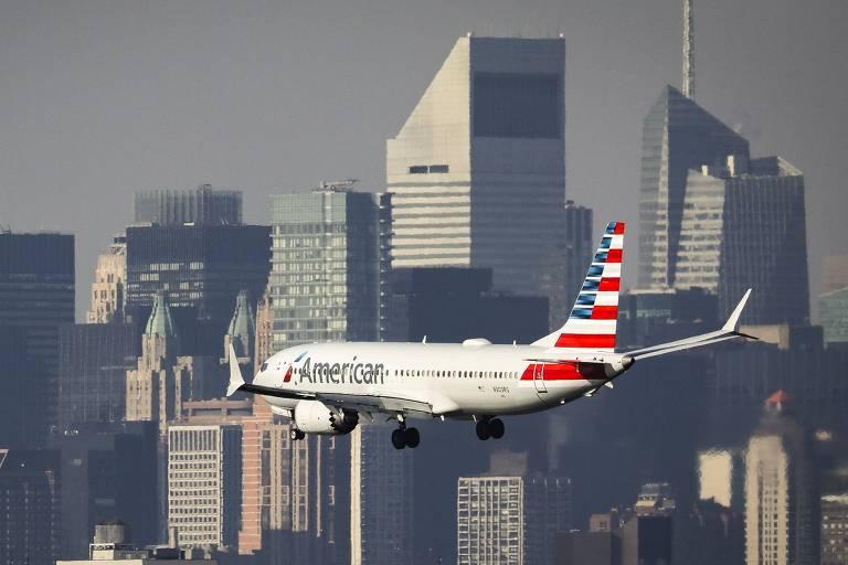 Avião em voo com cidade e prédios ao fundo