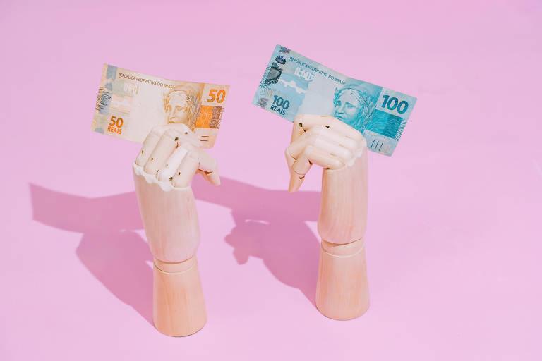 Duas mãos de madeira seguram uma nota de R$ 50 e outra de R$ 100